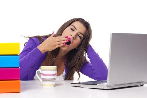 woman-yawning-coffee-books-and-laptop-desk